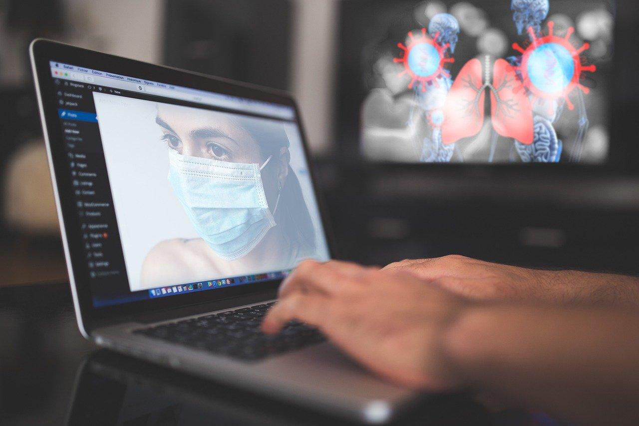Laptop mit Bild einer Person mit Mundschutz. Im Hintergrund eine stilisierte Lunge.