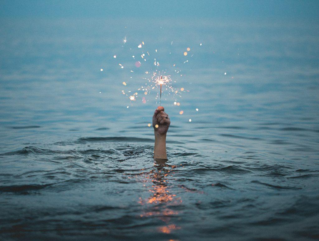 Hand mit Wunderkerze aus dem Wasser